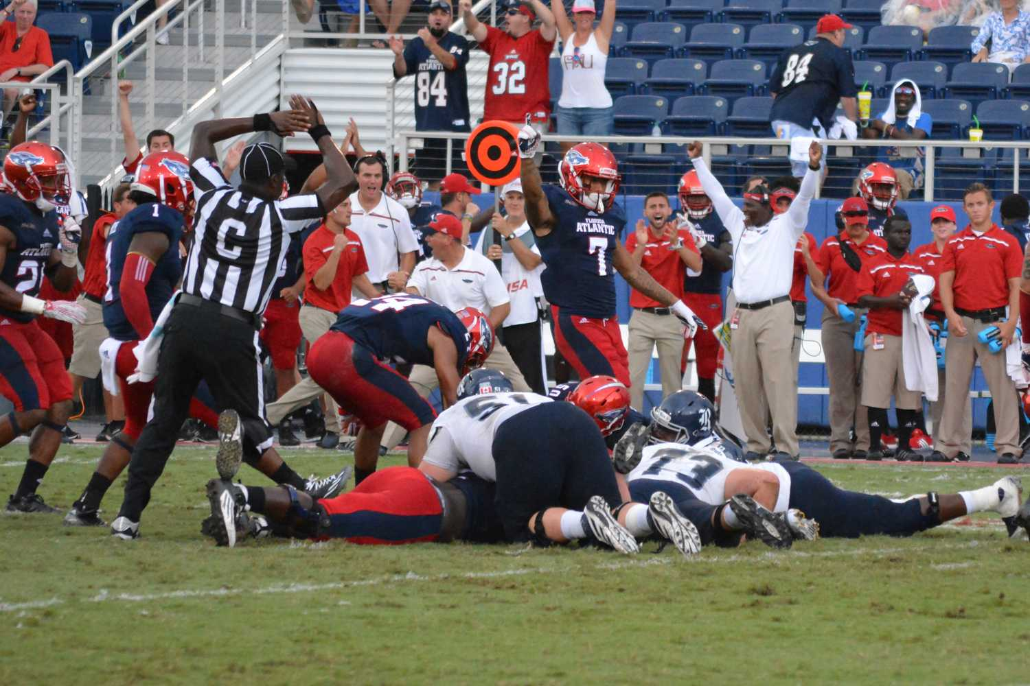 Freshman wide receiver Tavaris Harrison (7) and coaches celebrate after the FAU Owls take down Rice's offense. Emily Creighton | Features Editor