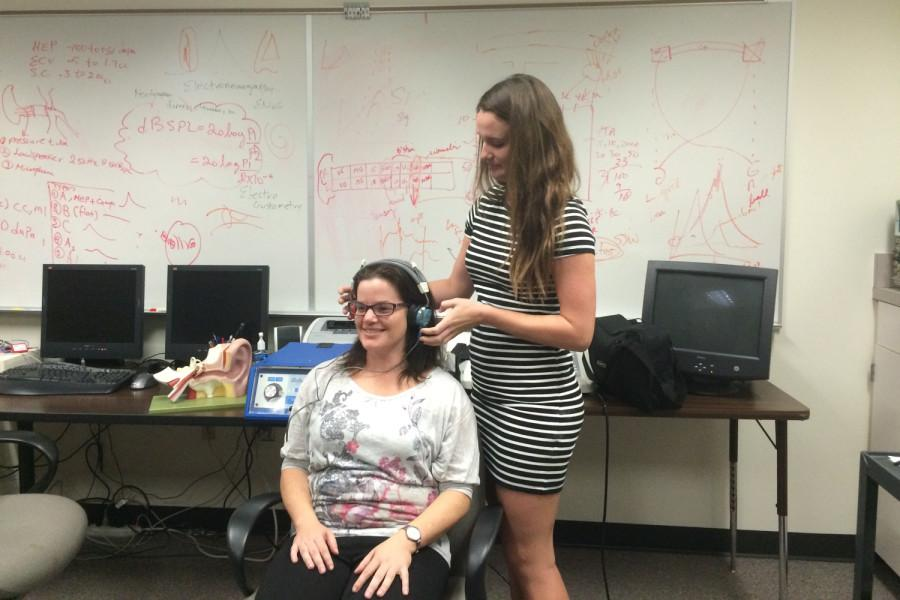 A Graduate student demonstrates the setup for the hearing screening process. Bibi Patel | Contributing Photographer