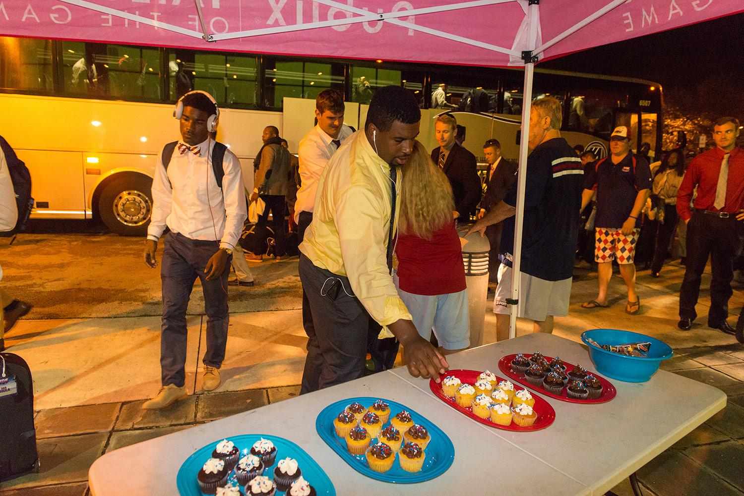 Quarterback Jaquez Johnson returning after a football game, welcomed warmly with cupcakes. Photo by Max Jackson