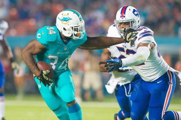 Miami Dolphins running back Damien Williams stiff arms linebacker Preston Brown during Miami's 22-9 win versus the Buffalo Bills last year. Max Jackson | Staff Photographer