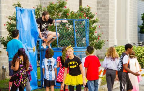 Children line up for their chance to take down Ph. D candidate Nathan Laza at FAU physics carnival.  Joseph Kennedy | Contributing Photographer