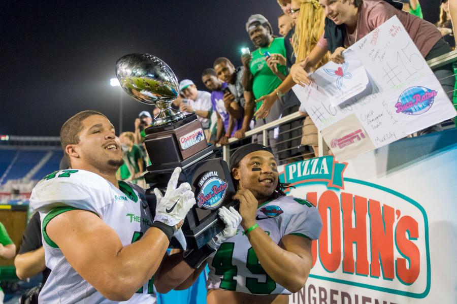 Running back Devon Johnson (left) and linebacker Cortez Carter of the Thundering Herd hold the Boca Raton Bowl trophy in front of their cheering fans during the inaugural game in 2014. Max Jackson | Staff Photographer