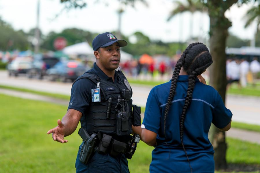 A police officer talks with a student at a home football game. Max Jackson | Staff Photographer