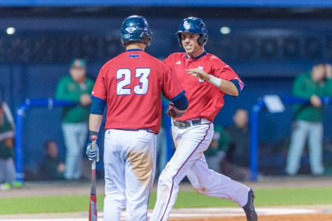 Junior shortstop C.J. Chatham is greeted at the plate by then senior outfielder Brendon Sanger (23) during the Owls' 5-3 win over the Miami Hurricanes on Feb. 18, 2015. Photo by Max Jackson | Staff  Photographer