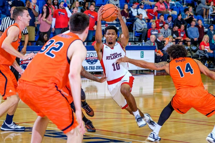 Freshman guard Nick Rutherford (10) tries to dribble past multiple UTSA defenders during FAU's 79-73 win on Feb. 11. Mohammed F Emran | Staff Photographer