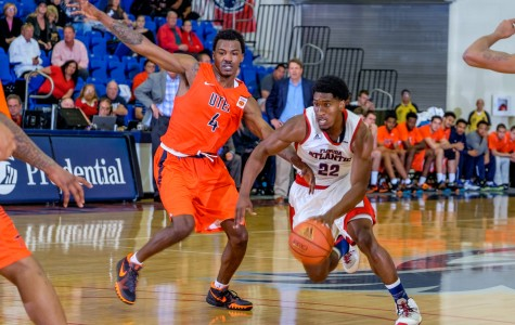 Senior guard Solomon Poole (22) dribbles past UTEP guard Lee Moore (4) for a layup during their game on Feb. 13. Mohammed F Emran | Staff Photographer