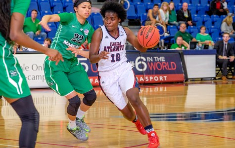 FAU senior guard Morgan Robinson (10) charges toward the basket while Marshall's Kiana Evans defends. Mohammed F Emran | Staff Photographer