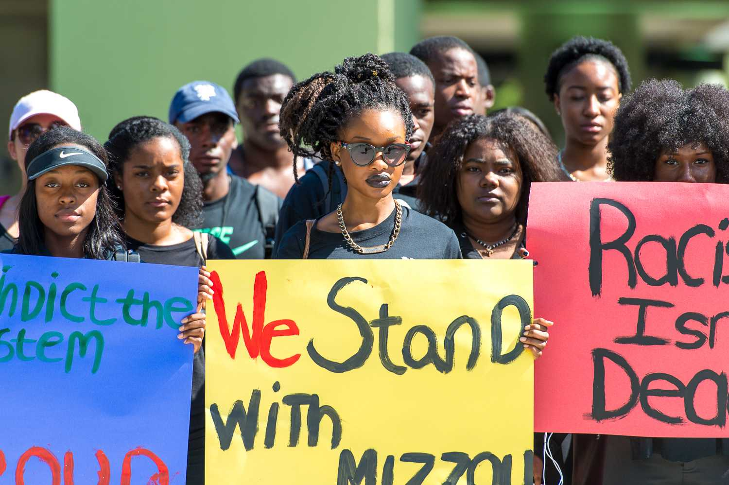 "Berlinie St. Fort, junior communications major (center) shows her support for students at the University of Missouri during a protest in November 2015. Some other signs said ""Racism isn't dead,"" and ""#indictthesystem Black and Proud."". Max Jackson 