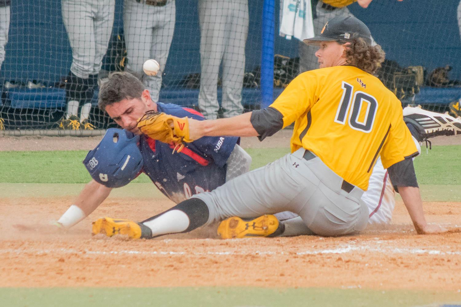 Junior shortstop CJ Chatham slides safely past the tag of University of Southern Missippi senior pitcher Jake Winston after a passed ball in the bottom of the sixth inning of the team's April 30 game. Ryan Lynch | Multimedia Editor