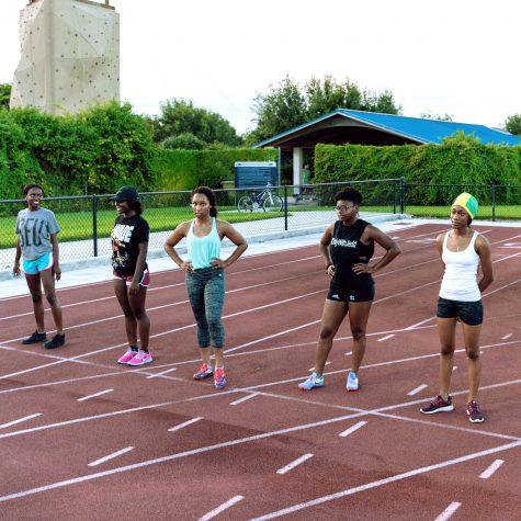 Participants in the Women's 100 meter race line up before the start of the event. Patrick Delaney | Photo Editor