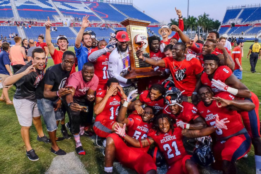 After one of the Owls' biggest wins of the season over in-state rival Florida International, fans and members of the team celebrate the victory with the Shula Bowl Trophy. Mohammed F. Emran | Staff Photographer