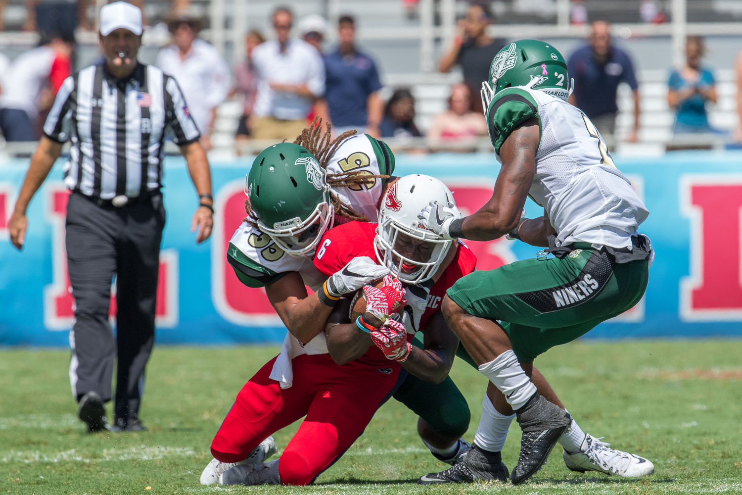 Charlotte redshirt freshman linebacker Tyriq Harris (35) and senior defensive back Kendrick Davis (2) take down FAU redshirt freshman running back Kerrith Whyte.