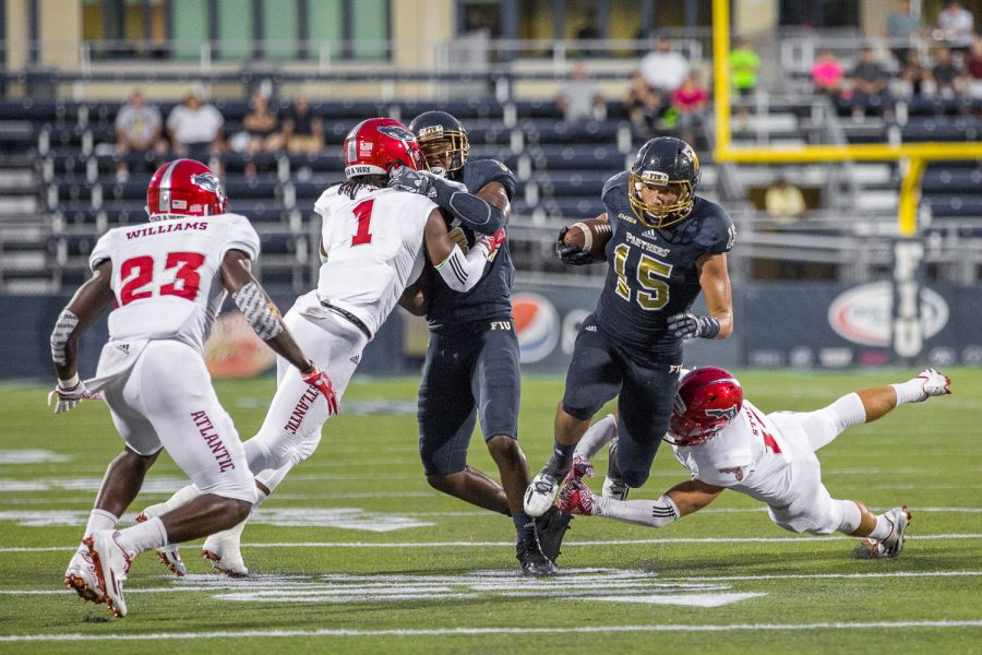 FIU redshirt freshman wide receiver Austin Maloney (15) slips through the hands of FAU redshirt sophomore defensive back Jake Stoshak. Maloney gained 55 yards for the Panthers against FAU Saturday night. Brandon Harrington | Staff Photographer