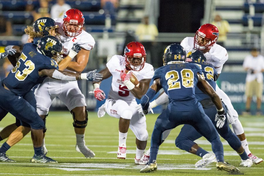 FAU freshman running back Devin Singletary (5) stares down FIU senior safety Deonte Wilson (28) as he rushes down the center of the field. Singletary rushed for 86 total yards against FIU Saturday night. Brandon Harrington | Staff Photographer