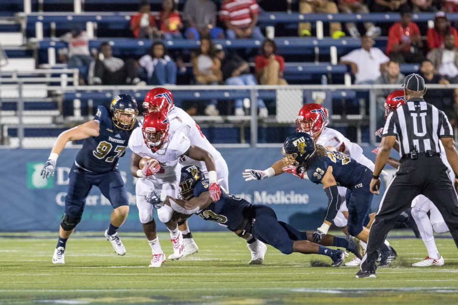 FAU freshman running back Devin Singletary (5) shakes off a tackle attempt by FIU junior linebacker Anthony Wint (53). Singletary scored one touchdown against FIU in the Shula Bowl. Brandon Harrington | Staff Photographer
