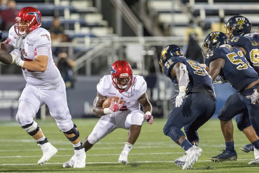 FAU freshman running back Devin Singletary (5) avoids being tackled by three FIU defenders in the first half against FIU in the Shula Bowl Saturday night. Brandon Harrington | Staff Photographer