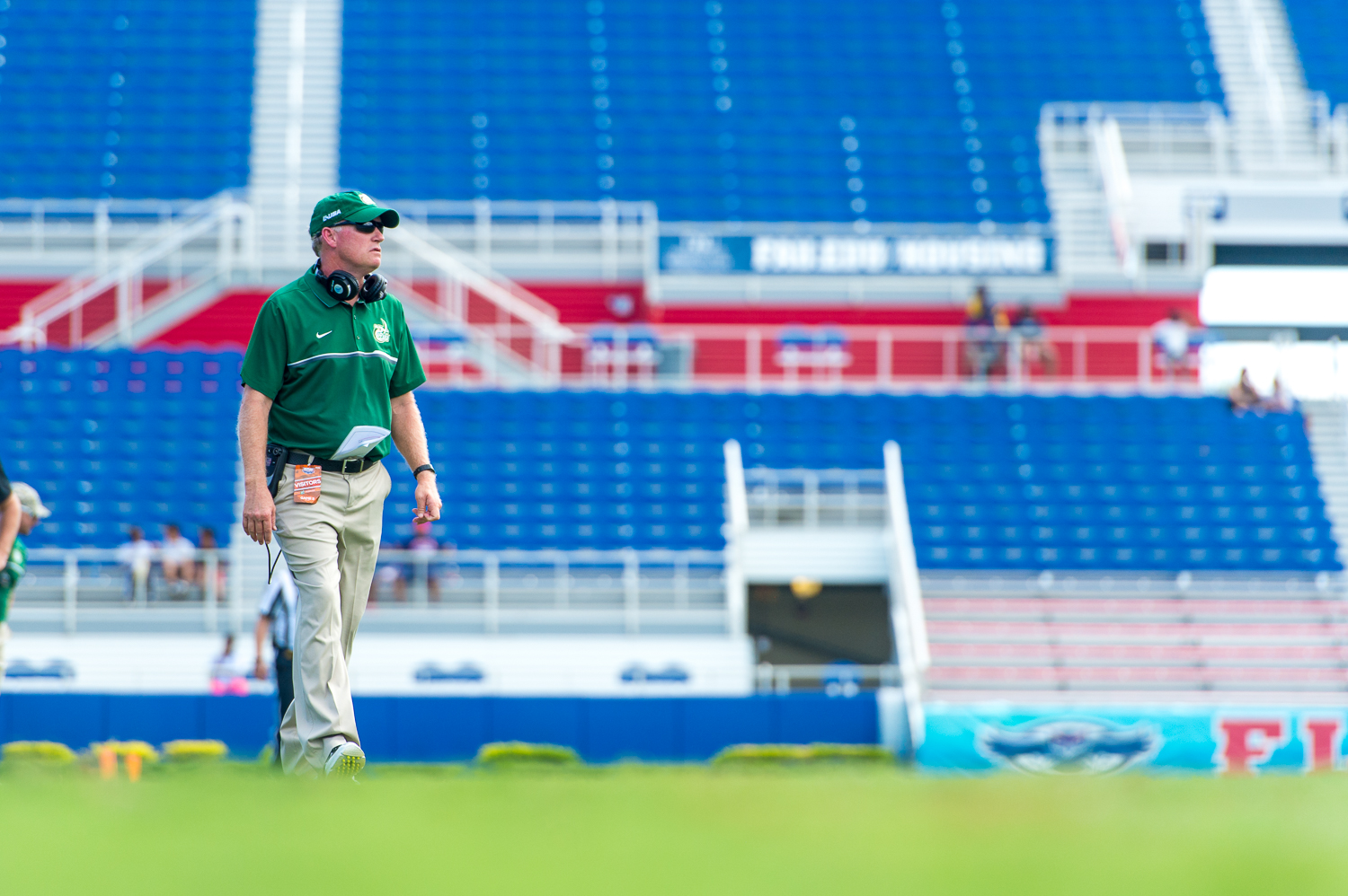 Charlotte head coach Brad Lambert walks onto the field after two consecutive false start penalties forced his punter to kick further in the endzone.