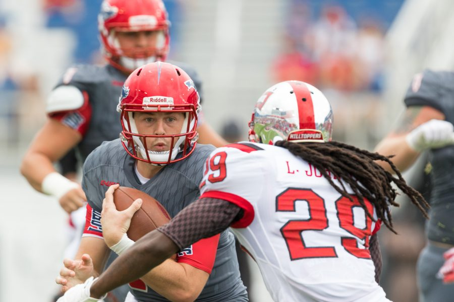 FAU redshirt sophomore quarterback Jason Driskel (16) runs through Western Kentucky junior defensive back Leverick Johnson (29) during Saturday's game. Brandon Harrington | Staff Photographer