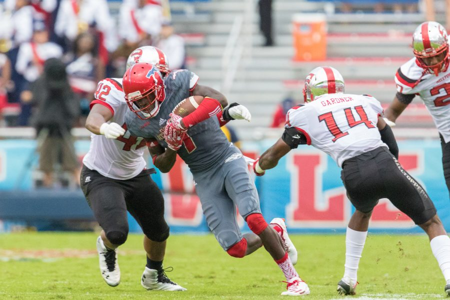 FAU redshirt freshman wide receiver Tavaris Harrison (7) rushes past Western Kentucky junior defensive back Juwan Gardner (14) before he is taken down by Western Kentucky junior defensive end Derik Overstreet (42). Brandon Harrington | Staff Photographer