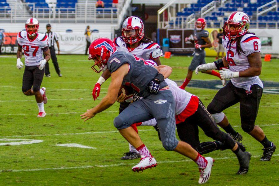Owls freshman quarterback Daniel Parr is tackled by redshirt senior defensive back Branden Lewsten. Jonathan Scott | Contributing Photographer