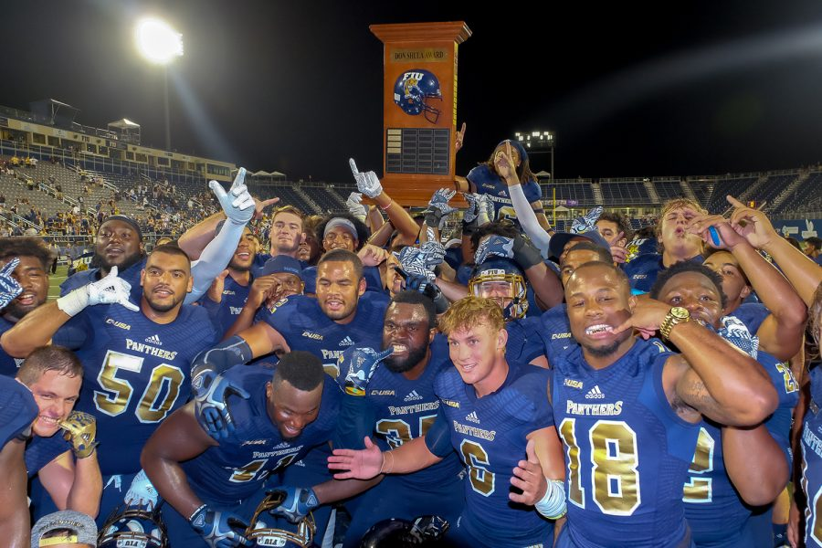 FIU players celebrate with the Shula Bowl trophy after winning against FAU 33-31. This was FIU's fourth Shula Bowl win ever. Mohammed F Emran | Staff Photographer