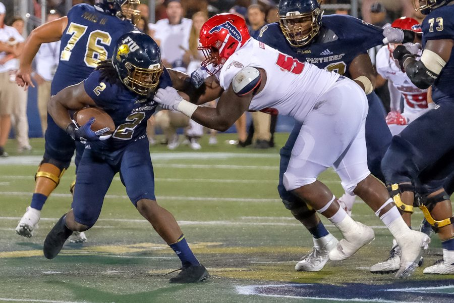 Panthers running back Anthony Jones (2) is tackled by Owls offensive line Reggie Bain (58). FIU did not earn any yards on the play. Mohammed F Emran | Staff Photographer