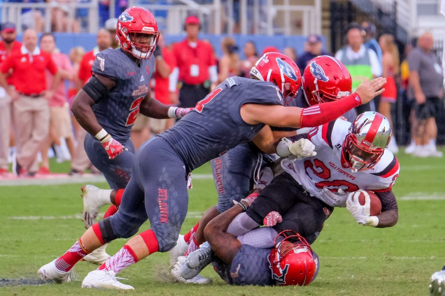 A trio of FAU defenders tackles Hilltoppers running back Anthony Wales(20). Mohammed F Emran | Staff Photographer