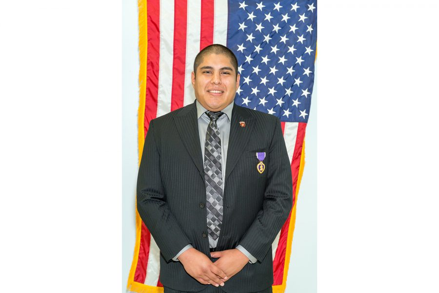 Alex Mera wears his purple heart medal in front of the United States Marine Corps and American flag. Brandon Harrington | Staff Photographer
