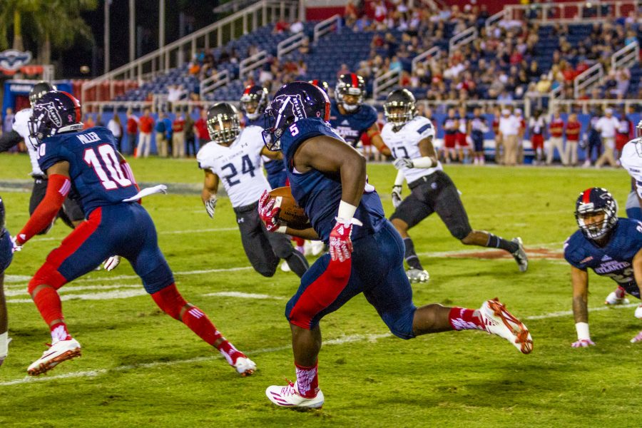 Alexis Hayward | Contributing Photographer Freshman running back Devin Singletary attempts to break a run down field.