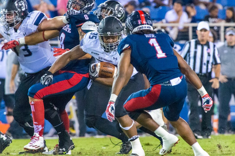 Max Jackson | Staff Photographer  Monarchs sophomore running back Jeremy Cox (35) eyes up Owls sophomore defensive back Ocie Rose (1) before being tackled. Cox ran for 63 yards on the night.