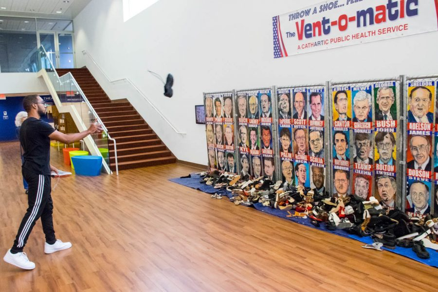 """Freshman Kymani Lewis throws a shoe at """"The Vent-o-matic,"""" which allows visitors to throw a shoe at the Republican party member of their choosing. Craig Ries 