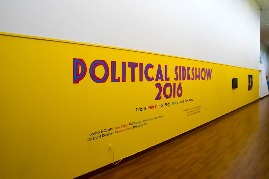 """FAU's Gender and Women's Studies Professor and """"Political Slideshow 2016"""" curator/creator Jane Caputi Poses for a photo with her favorite piece from the election exhibit. Craig Ries 