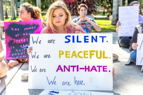 Natasha Roberts a sophomore Communications major sits with the group of protesters holding a sign signalling the message of their goal: a silent, peaceful, anti-hate protest. Alexis Hayward | Contributing Photographer