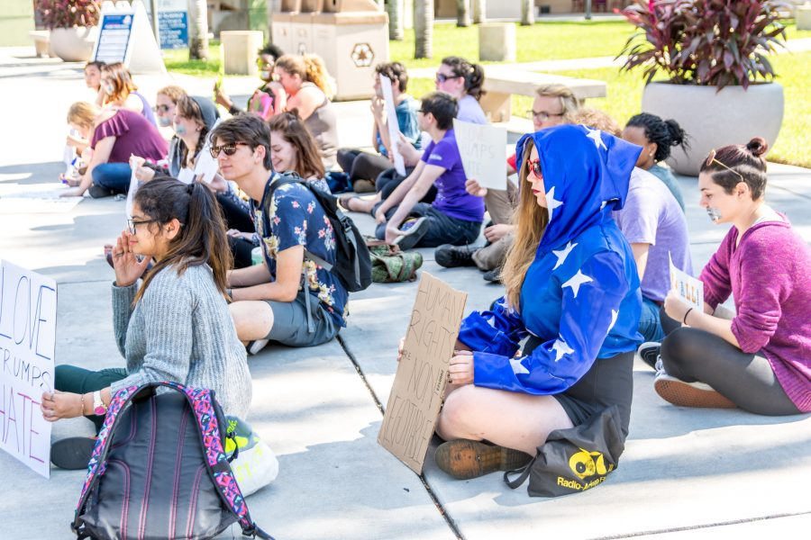 A group of silent protests sit outside the Social Sciences building. Alexis Hayward | Contributing Photographer