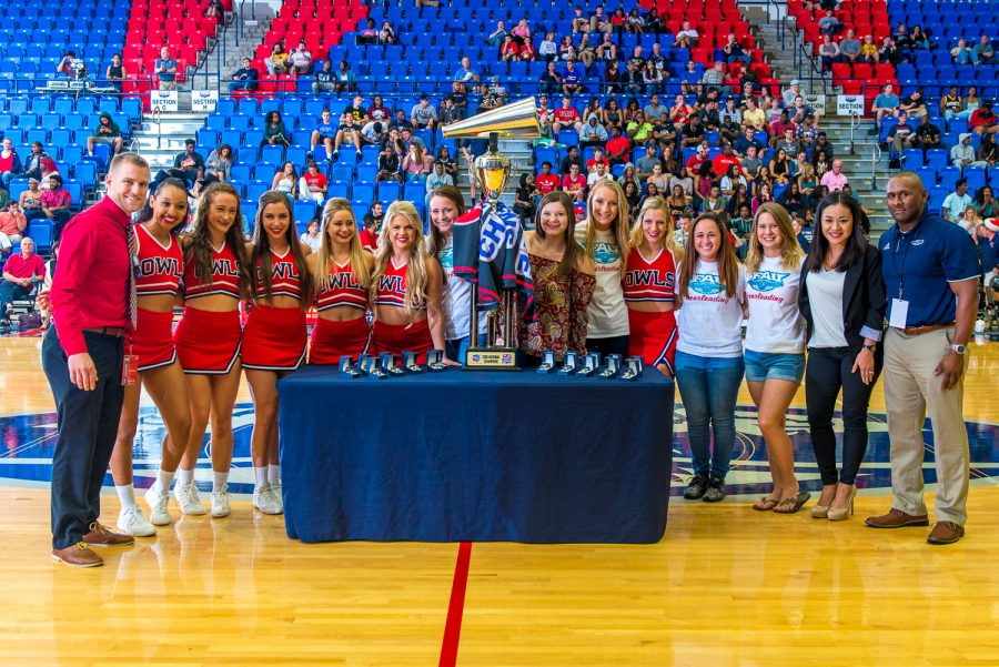 The+FAU+Cheer+team+poses+with+their+national+championship+rings+and+trophy+during+halftime+of+an+Owls+basketball+game+in+early+December.+Max+Jackson+%7C+Staff+Photographer