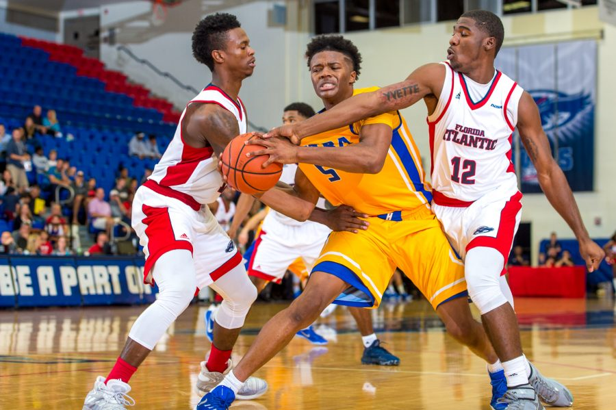 FAU forward Marcus Neely (13) and guard Devorious Brown (12) foul Hofstra guard Eli Pemberton (5) to stop the clock with less than a minute left in the game.