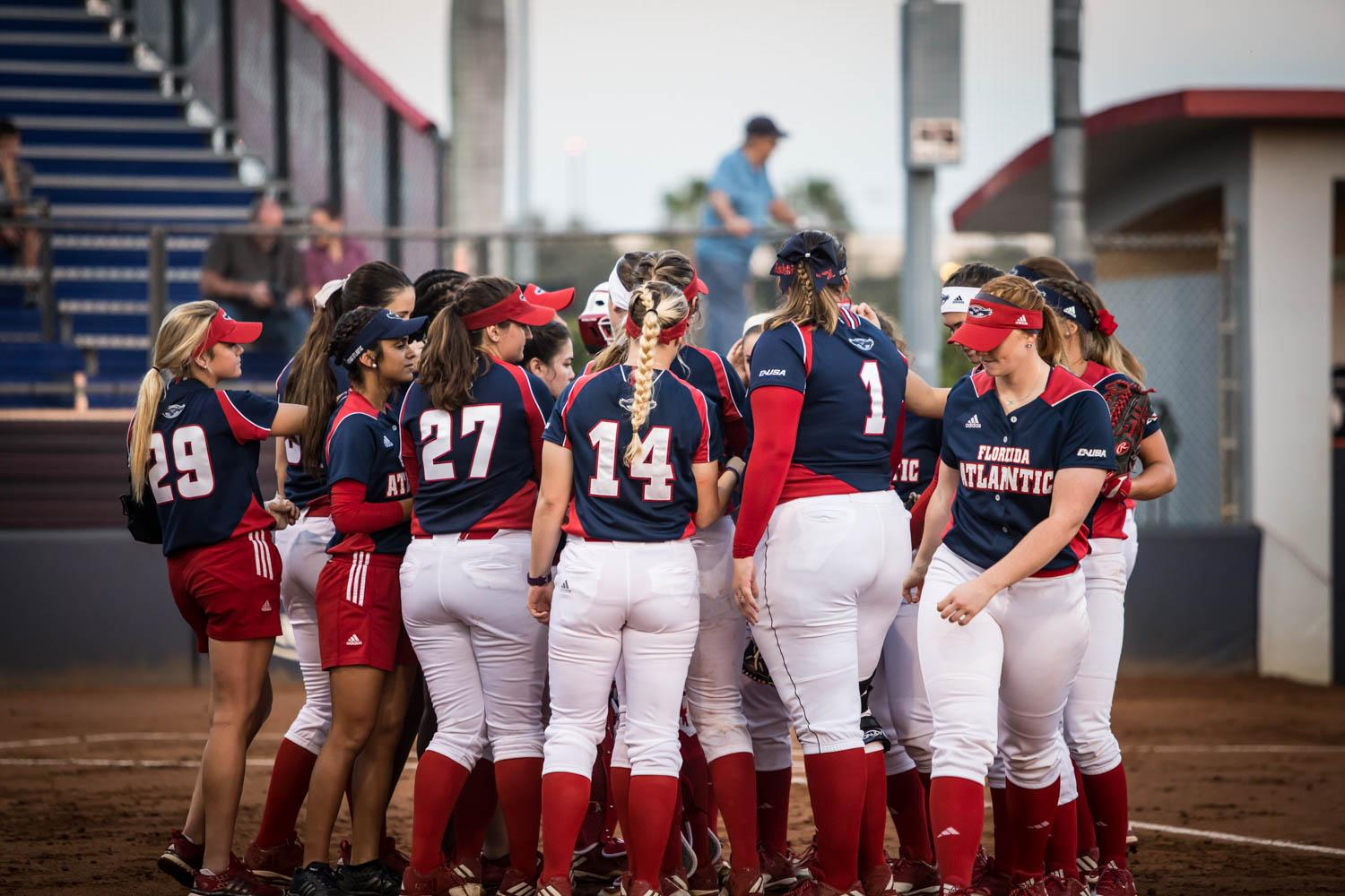 FAU Softball players and coaches huddle up in front of their dugout after splitting a doubleheader against the University of North Florida on Feb. 9. Alexander Rodriguez | Contributing Photographer