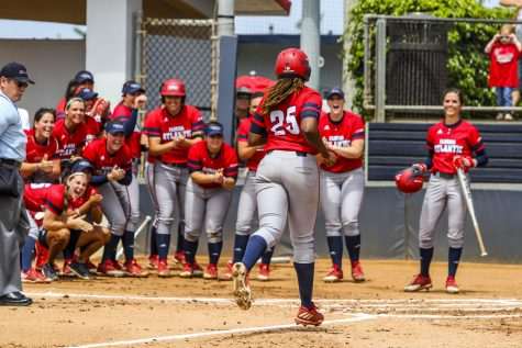 The Owls wait for junior Emily Lochten to cross home plate after her 15th home run of the season. Alexander Rodriguez | Contributing Photographer
