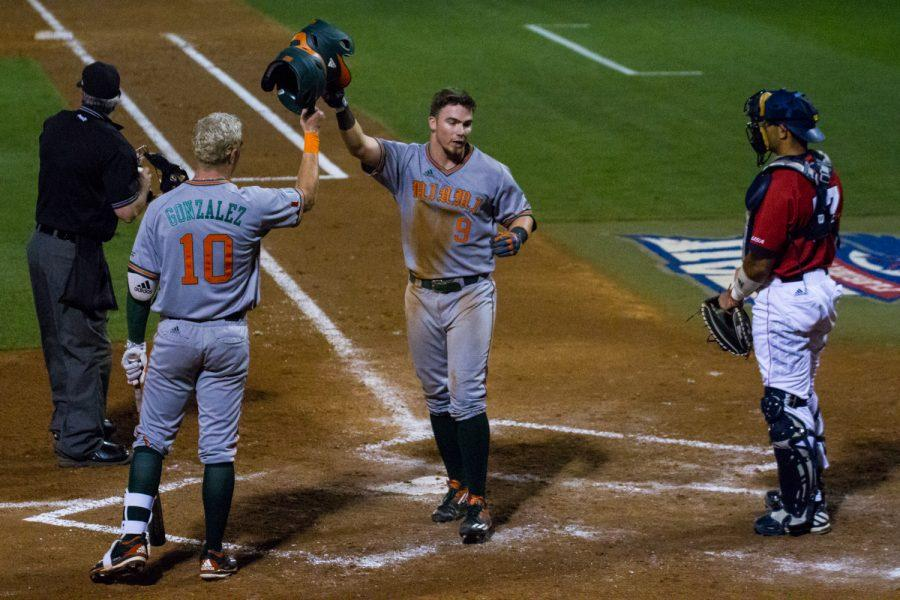Miami's Carl Chester celebrates at the plate with Romy Gonzalez after hitting a solo home run in the top of the third inning to give the Hurricanes their first lead of the game 1-0. Ryan Lynch | Editor in Chief