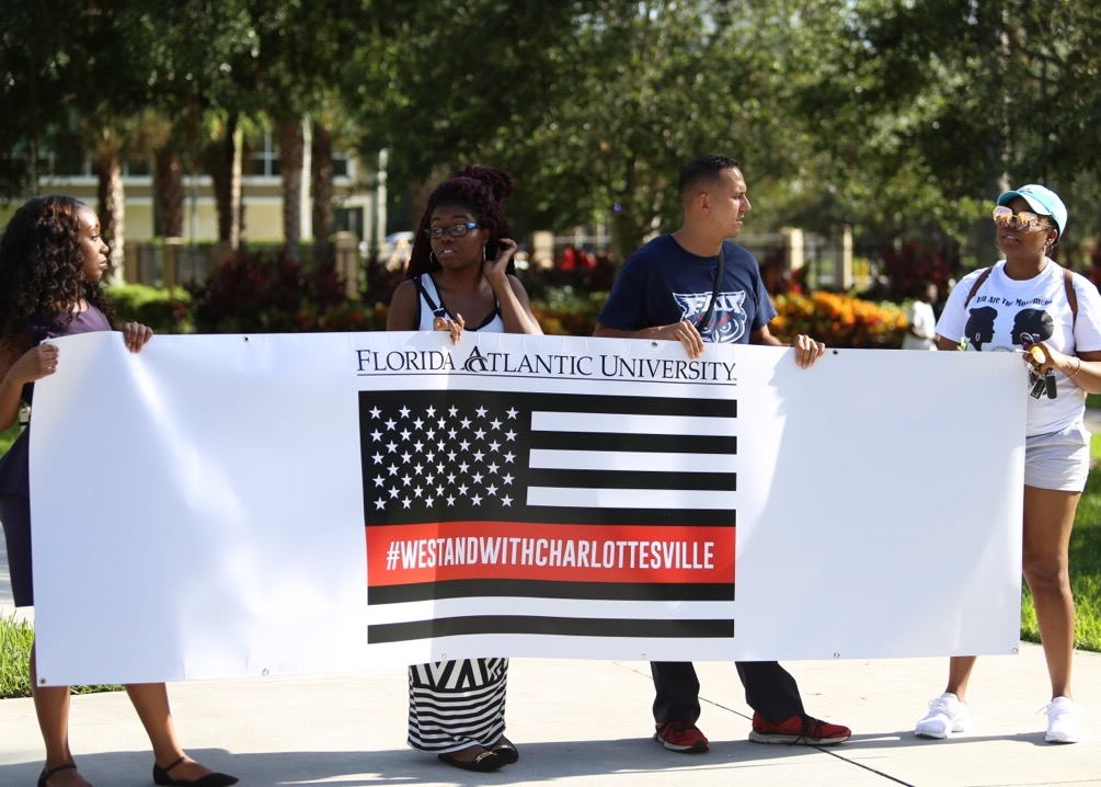 (From left to right) Student body Governor Der'Resha Bastien, Jordan Bowles, Marek Madro and Khalia Moore hold the #WeStandWithCharlottesville banner at the beginning of the march. Photo by Alex Rodriguez | Photo Editor
