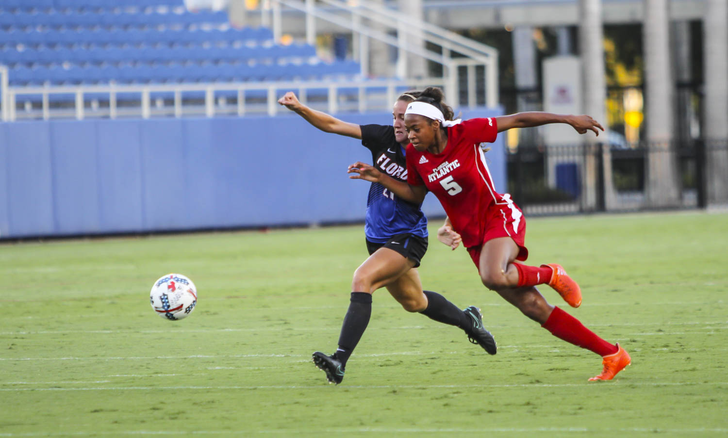 FAU forward Elisha Holmes (5) attempts to reach the soccer ball first before Florida defender Julia Lester (20).