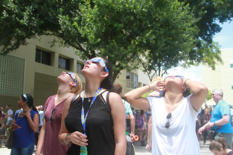 Freshman political science major Amanda Marrero (left), freshman multimedia journalism major Karla Recio (center), and freshman environmental science major Veronica Teek look up at the eclipse with their protective glasses.
