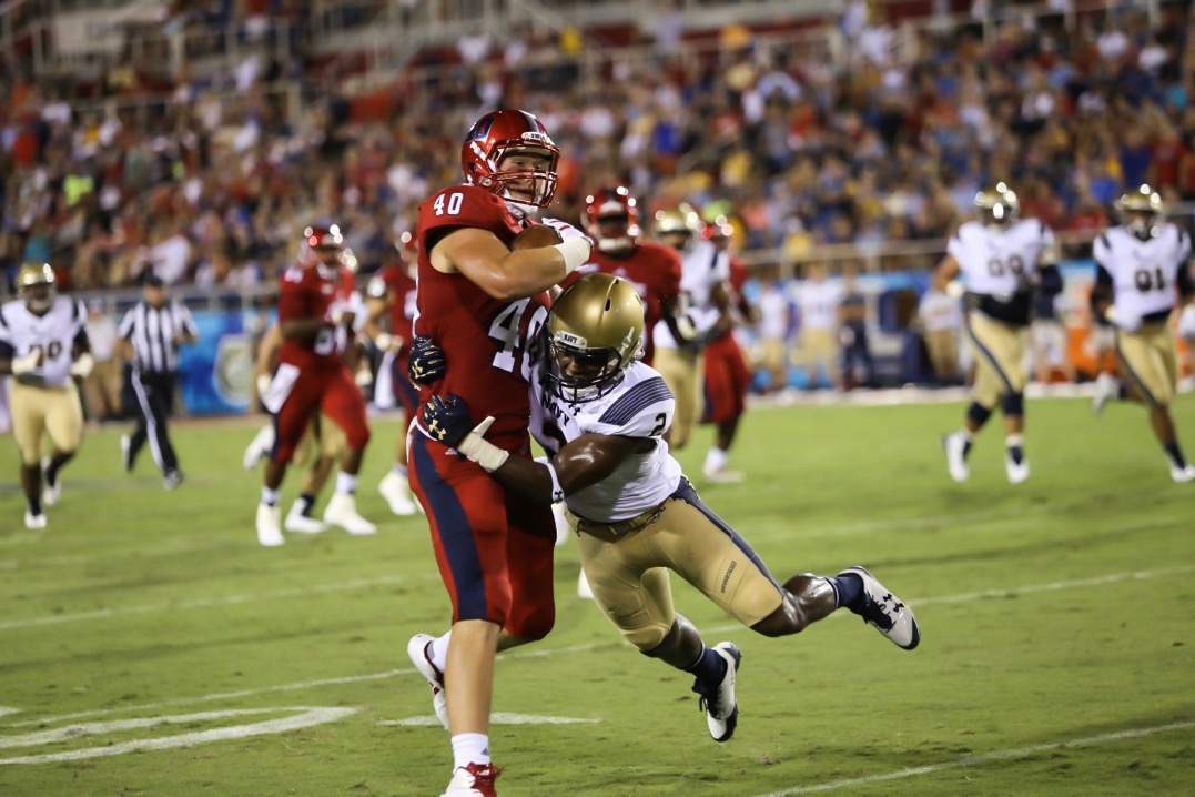 FAU sophomore tight end Harrison Bryant (40) is tackled by a Navy defensive player after making a catch during the Owls' loss to Navy Friday. Alexander Rodriguez | Photo Editor