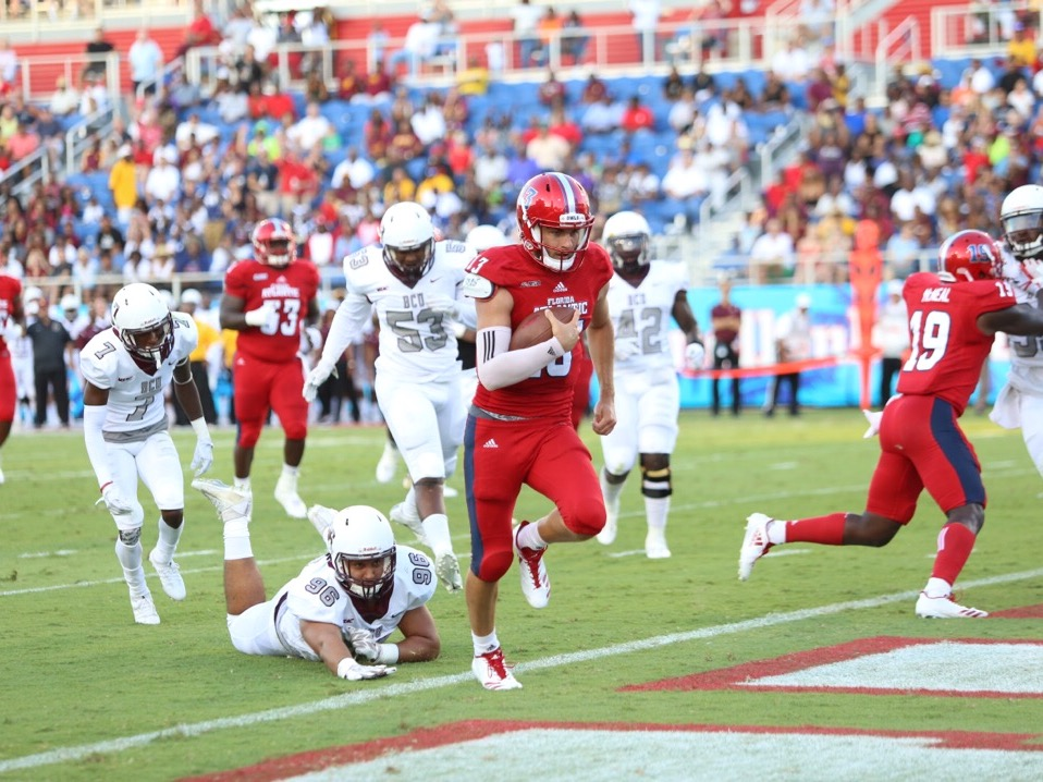 FAU redshirt sophmore quarterback Daniel Parr (13) runs toward the end zone to score FAU's first touchdown against Bethune-Cookman. Parr had two rushing touchdowns on the night. Alexander Rodriguez | Photo Editor
