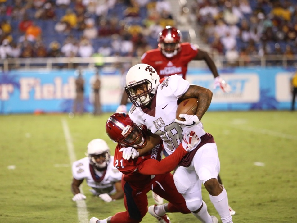 bb96cb2fe FAU defensive back Herb Miller (21) tackles Bethune Cookman s running back  Que shaun Byrd (38).