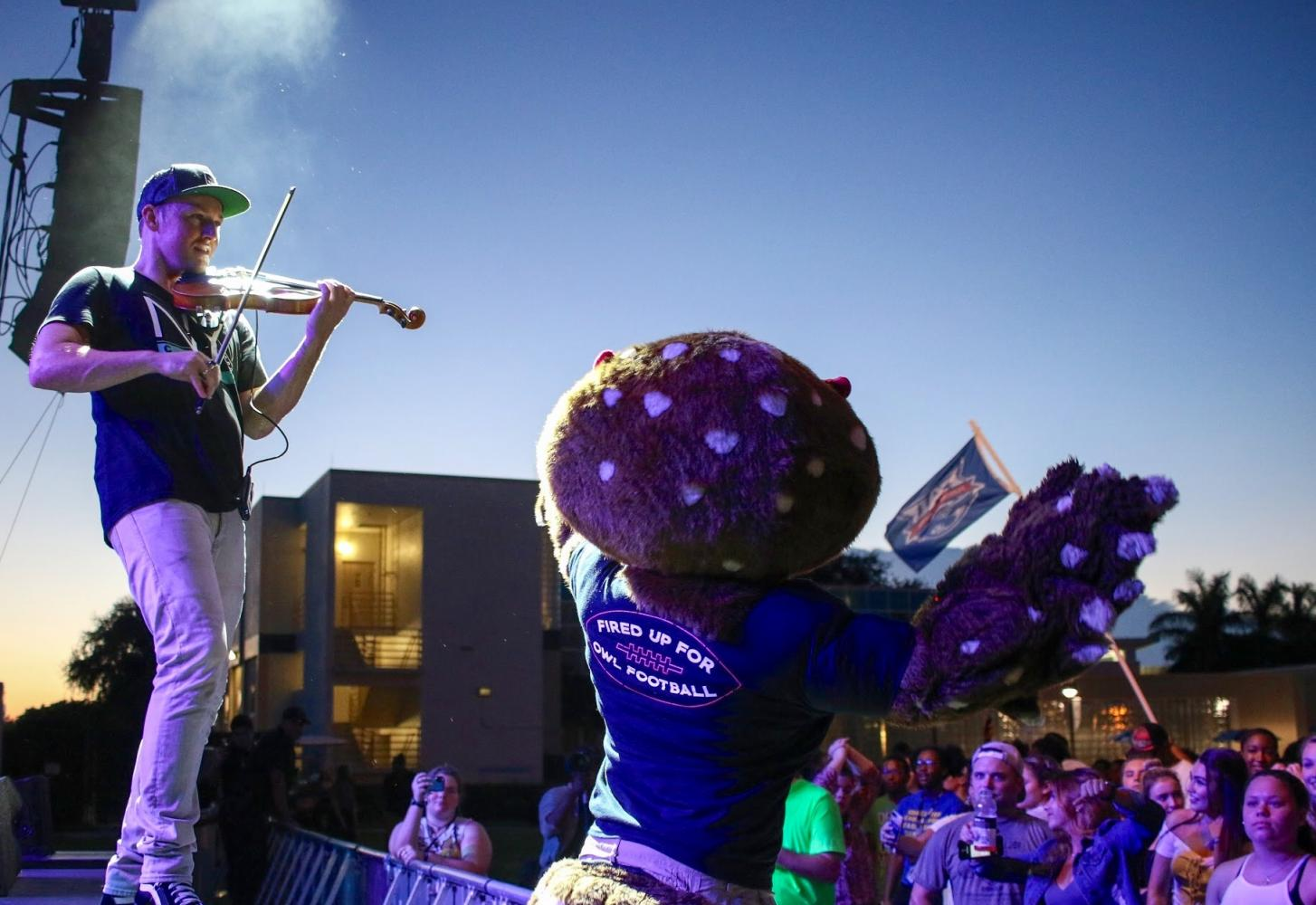 FAU's mascot Owlsley helps the opening act, hip-hop violinist Josh Vietti, get the crowd dancing during his performance. Joshua Giron | contributing photographer.