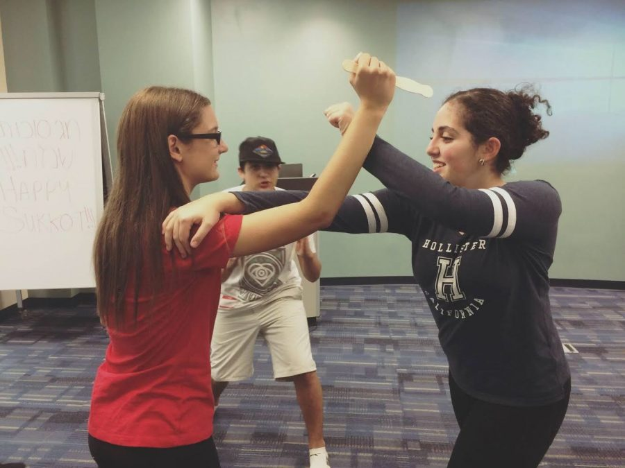 Joelle Dwek (right) attempts to prevent a fake knife attack from Shelby Klein (left), while Adam Golden (middle) helps direct their movements. Photo courtesy of Betsy Lempert
