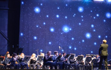 """Music conductor Kyle Prescott leads the Wind Ensemble through a theme song from the Pixar movie """"Incredibles"""" on Sunday night during the Band-O-Rama that was held at Mizner Park Amphitheater. Photo by Violet Castano"""