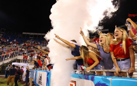FAU fans cheer and scream through the smoke as FAU sophomore running back Devin Singletary (5) scores a touchdown. Matthew Quick | Contributing Photographer