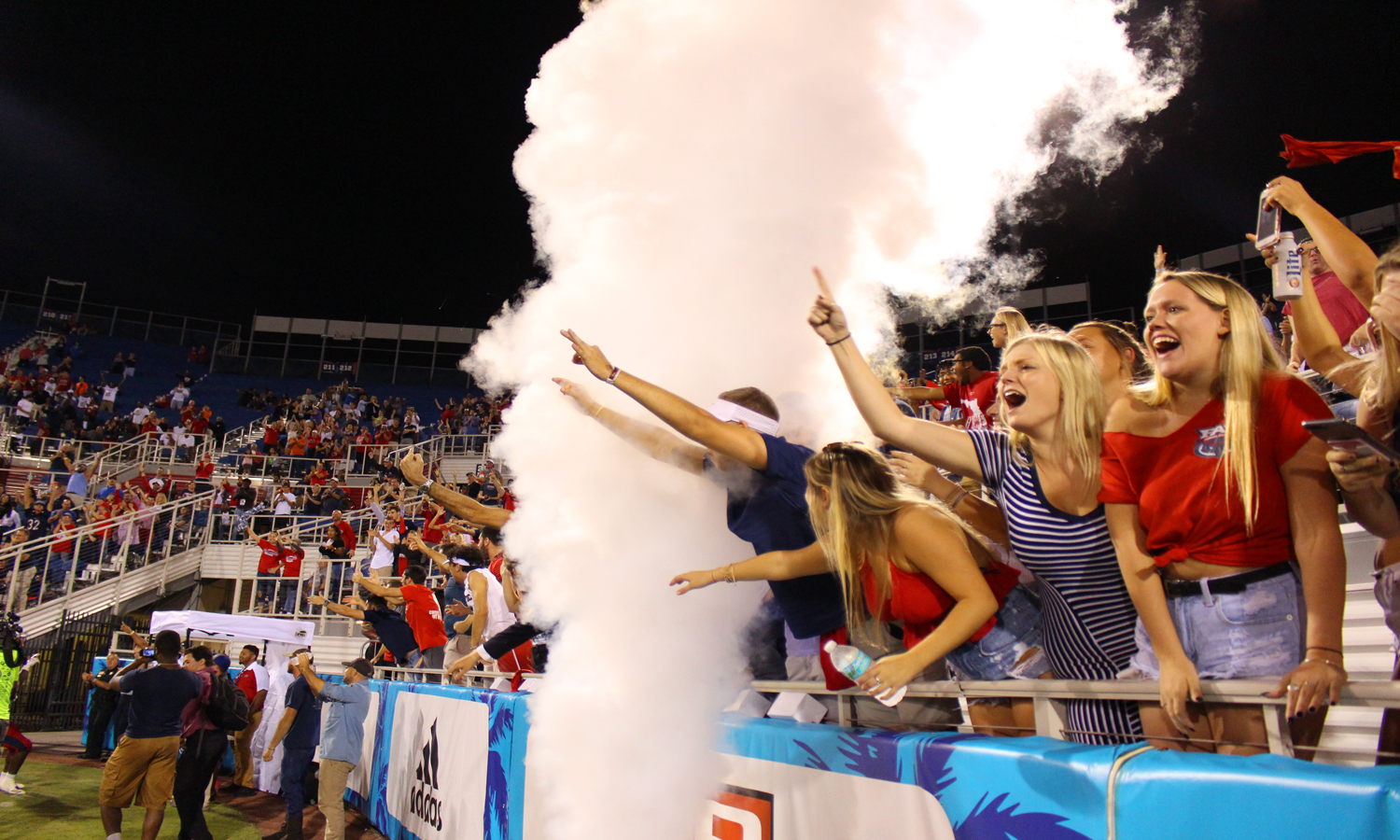 FAU fans cheer and scream through the smoke as FAU sophomore running back Devin Singletary (5) scores a touchdown. Matthew Quick   Contributing Photographer
